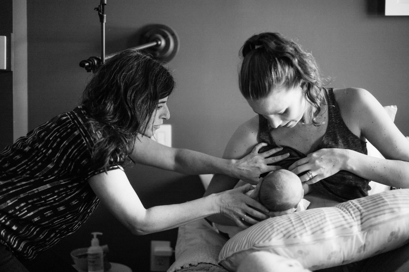 Nursing pro assisting a new mother and her newborn with breastfeeding.