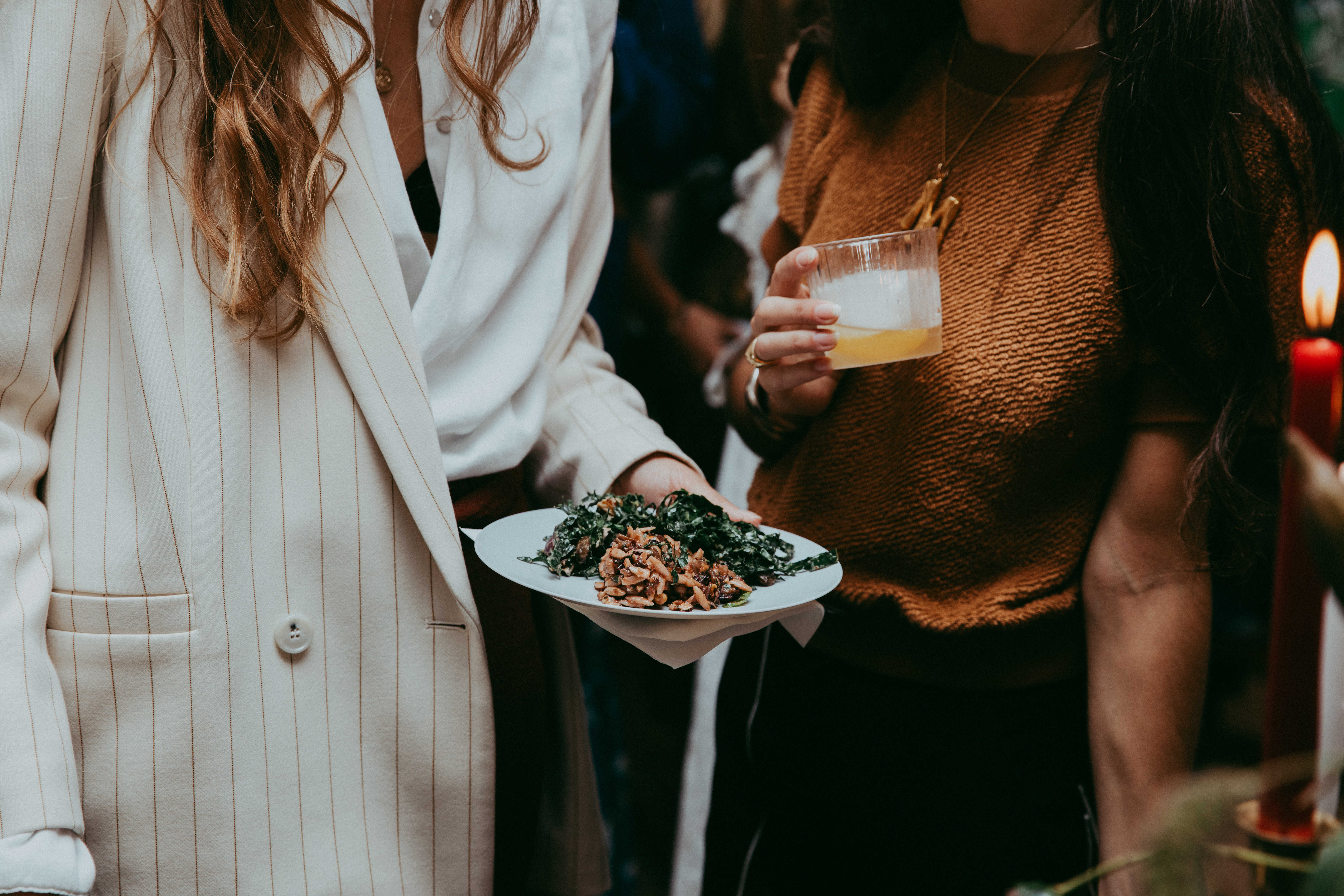 Two cocktail party guests enjoying a cocktail, small bites and conversation.