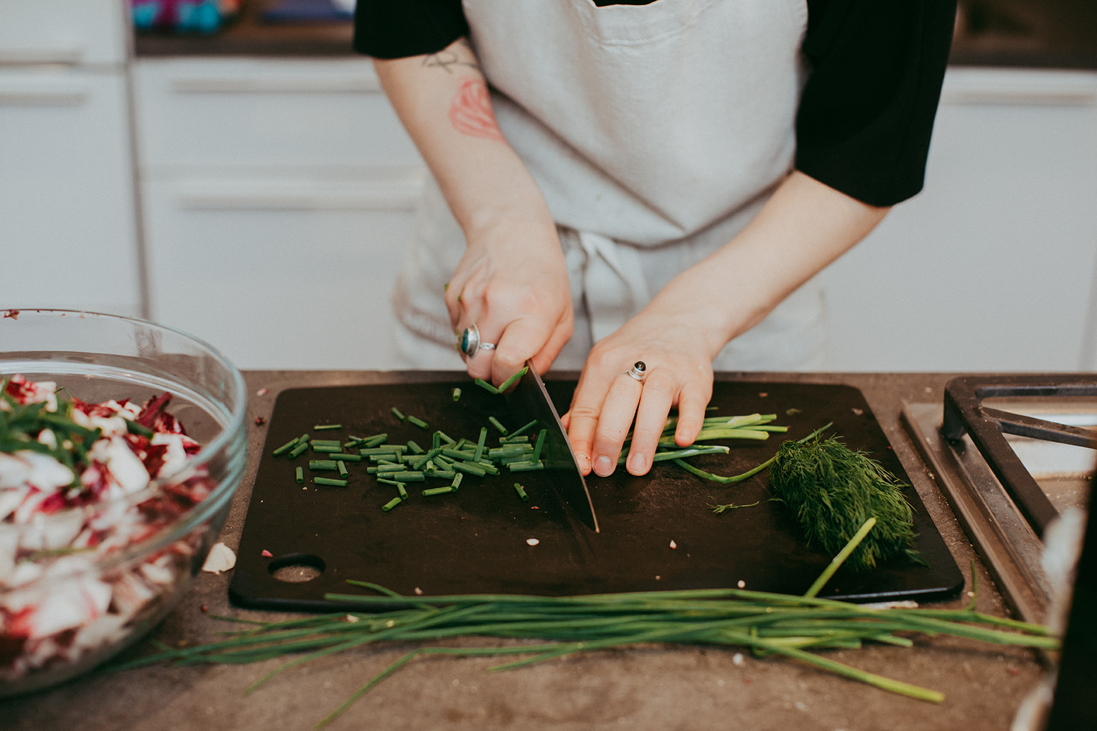 Chef chopping chives, dill and other plants as dinner preparation.
