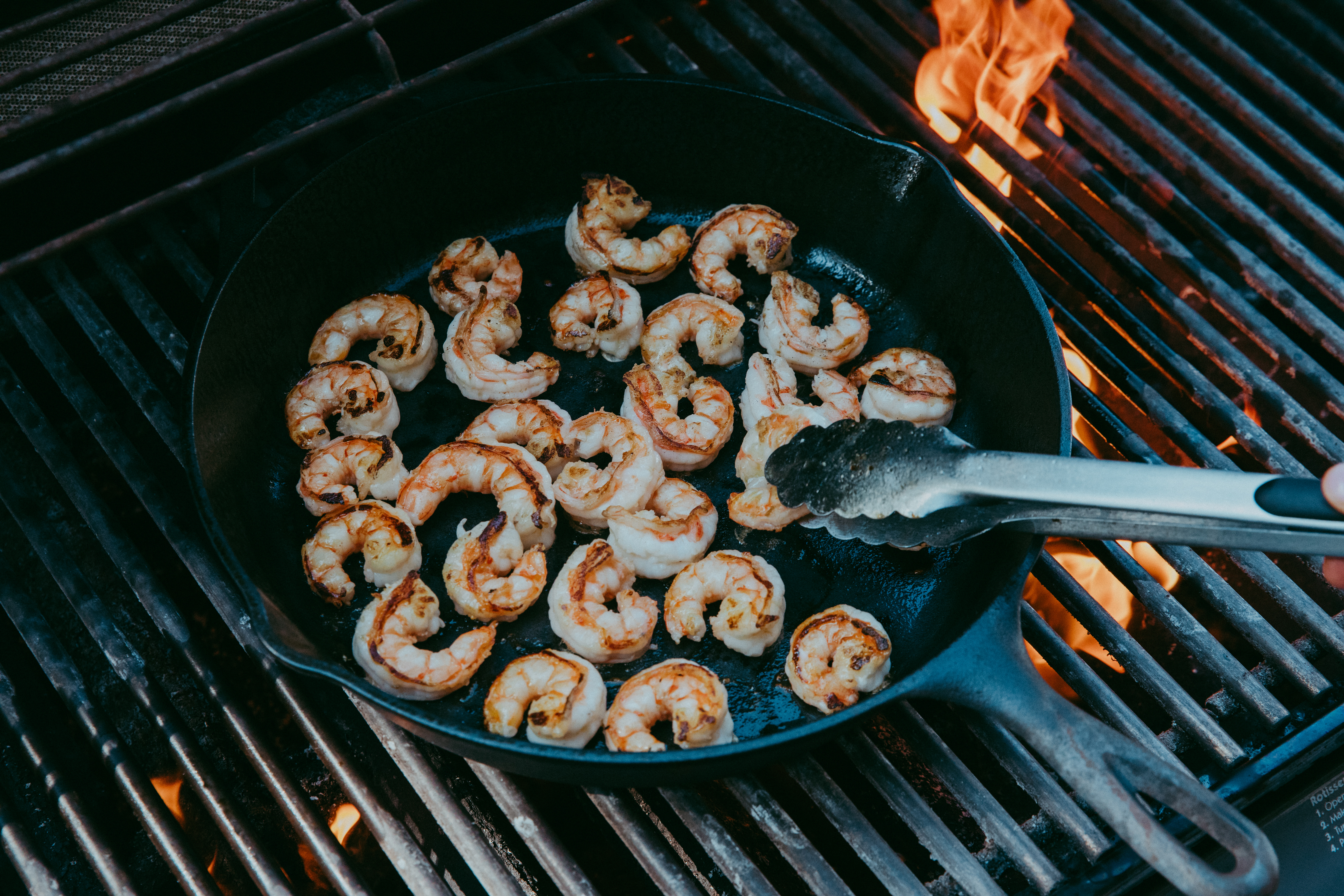Seasoned shrimp being flipped with tongs in a cast iron on a grill.